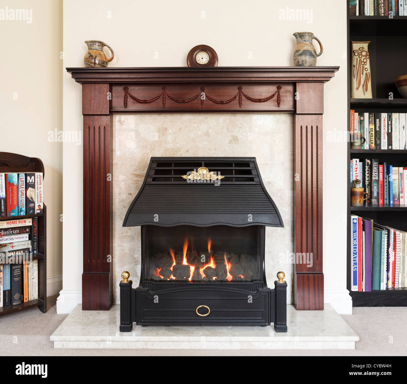 fireplace and gas fire lit in a uk house living room stock photo