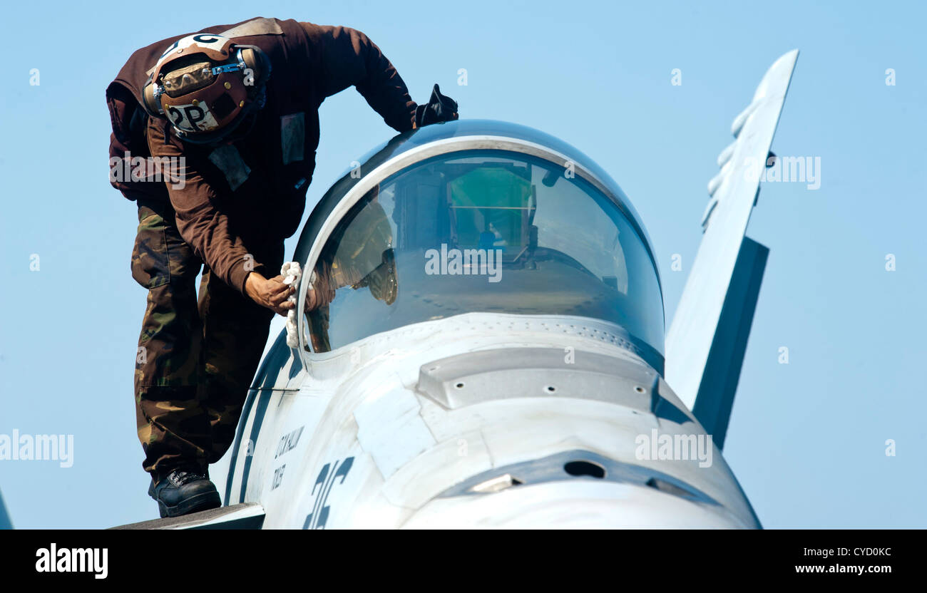 A plane captain wipes down the canopy window of an F/A-18E Super Hornet assigned to the  Tophatters  of Strike Fighter Squadron (VFA) 14 on the flight deck ... & A plane captain wipes down the canopy window of an F/A-18E Super ...