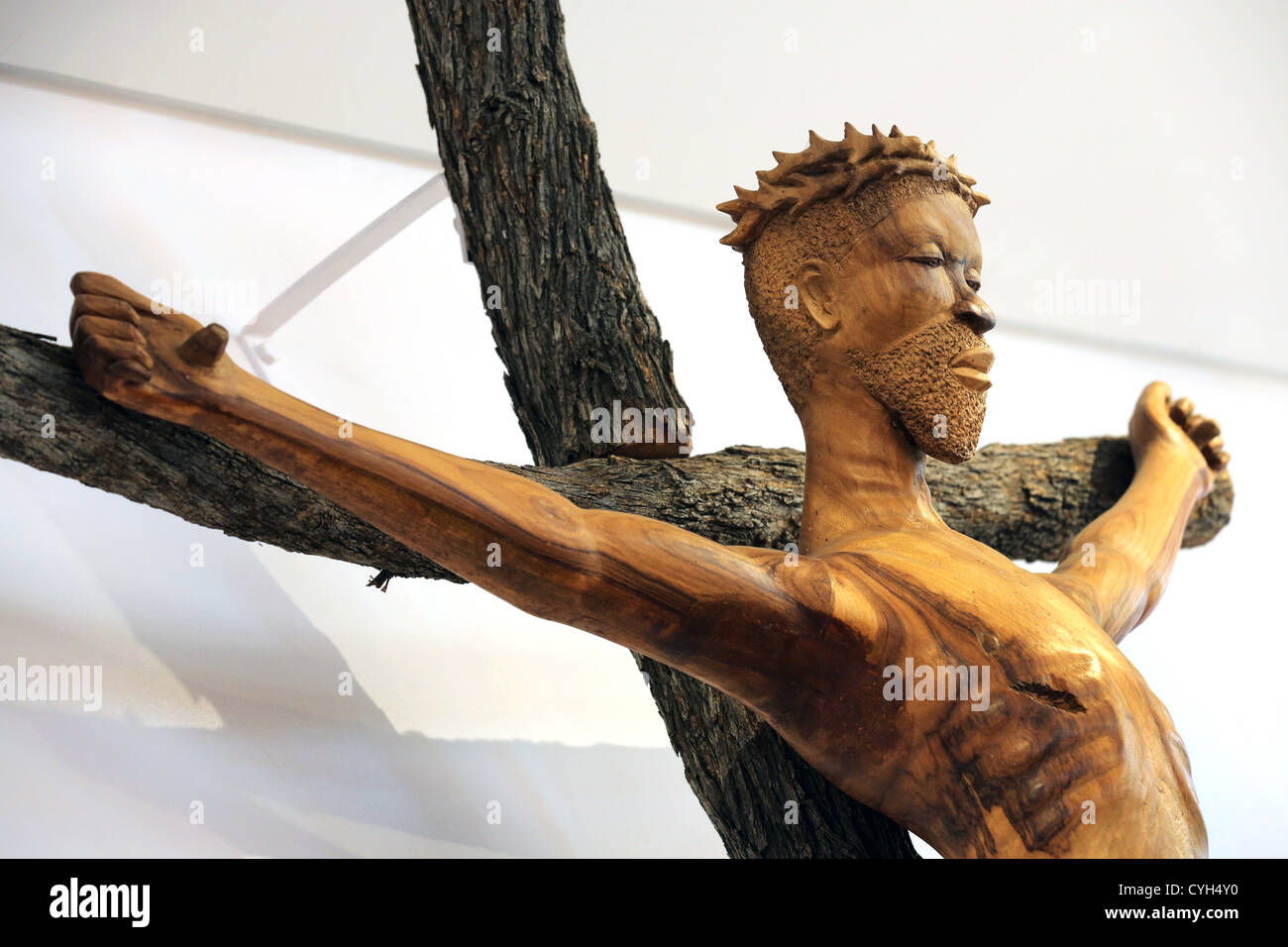 a wooden african statue of jesus christ on the cross with crown of