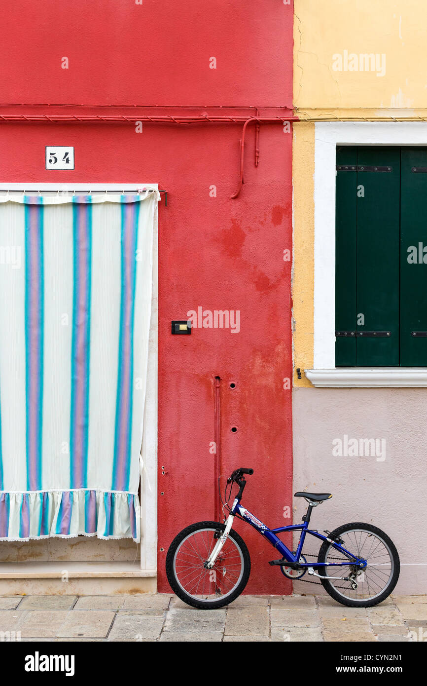 Blue Bicycle Standing Outside A Deep Red Painted House With A Pink, Blue  And White Striped Curtain