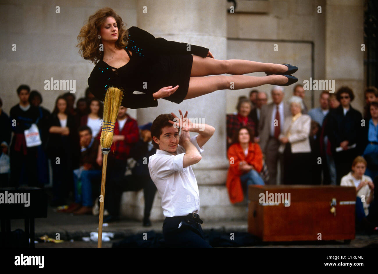 A young magician performs a levitation trick using a lady ... Female Magician Assistant