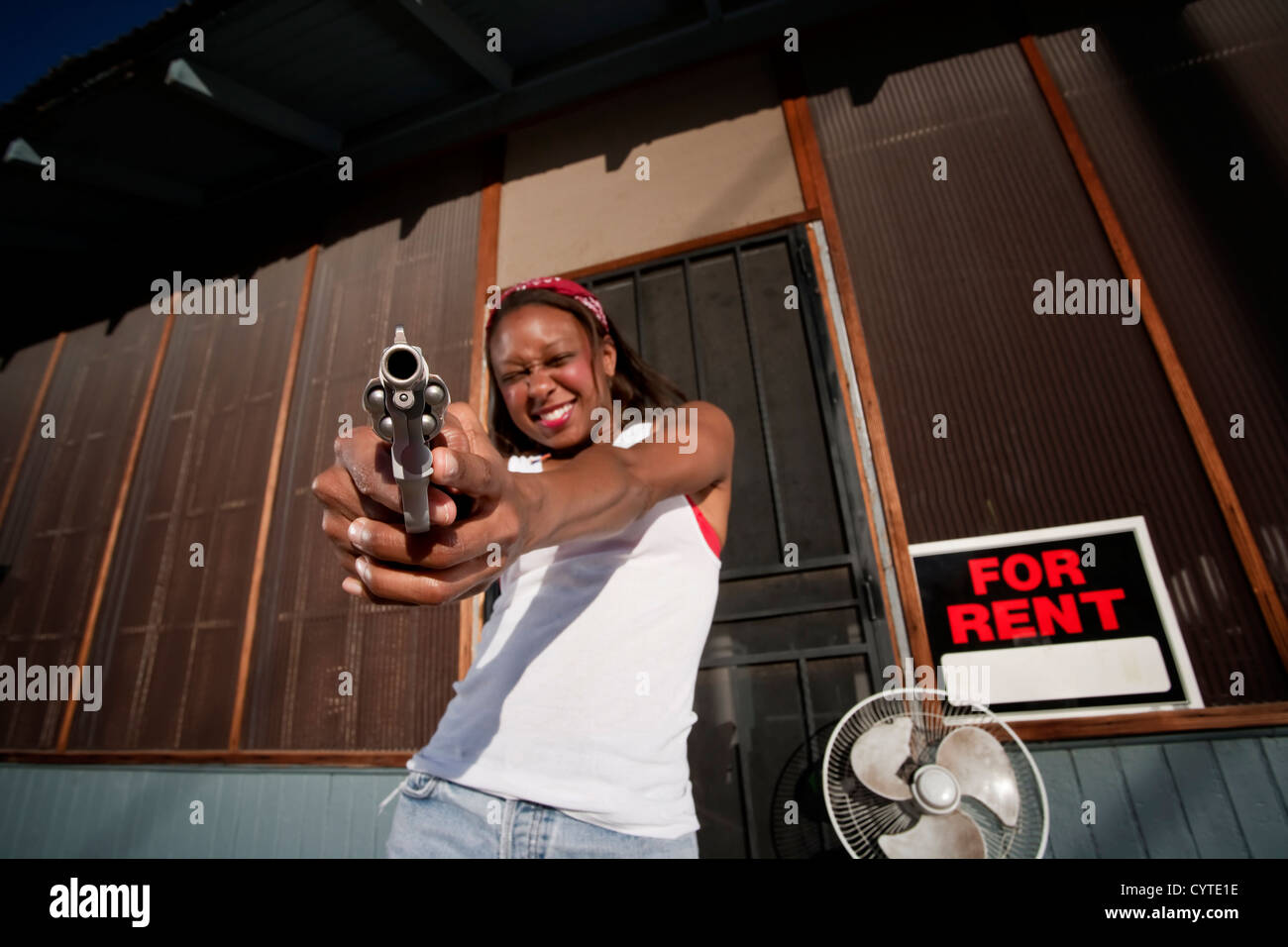 African american woman with a gun on her front porch