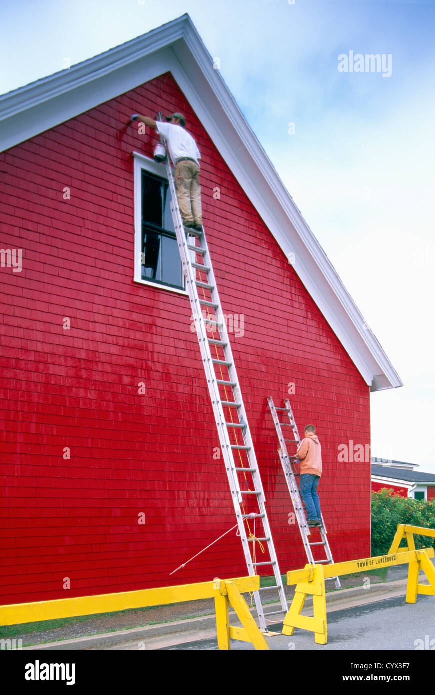 Exterior Wall Ladders : Painters standing on ladders painting bright red paint
