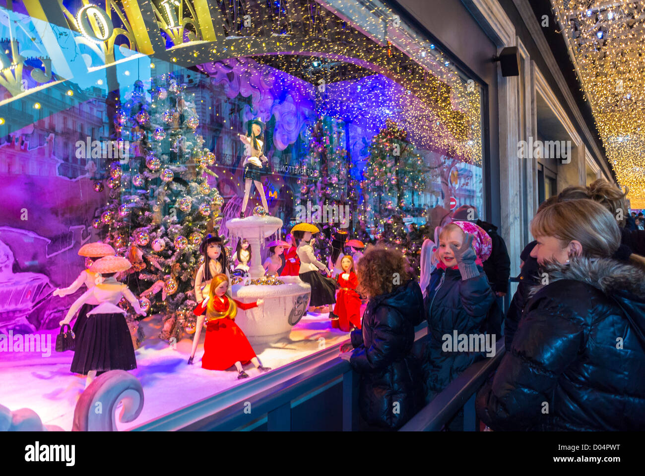 paris france families looking french department store le printemps dior shop front window enjoying christmas lights decorations display at night - Christmas Light Store