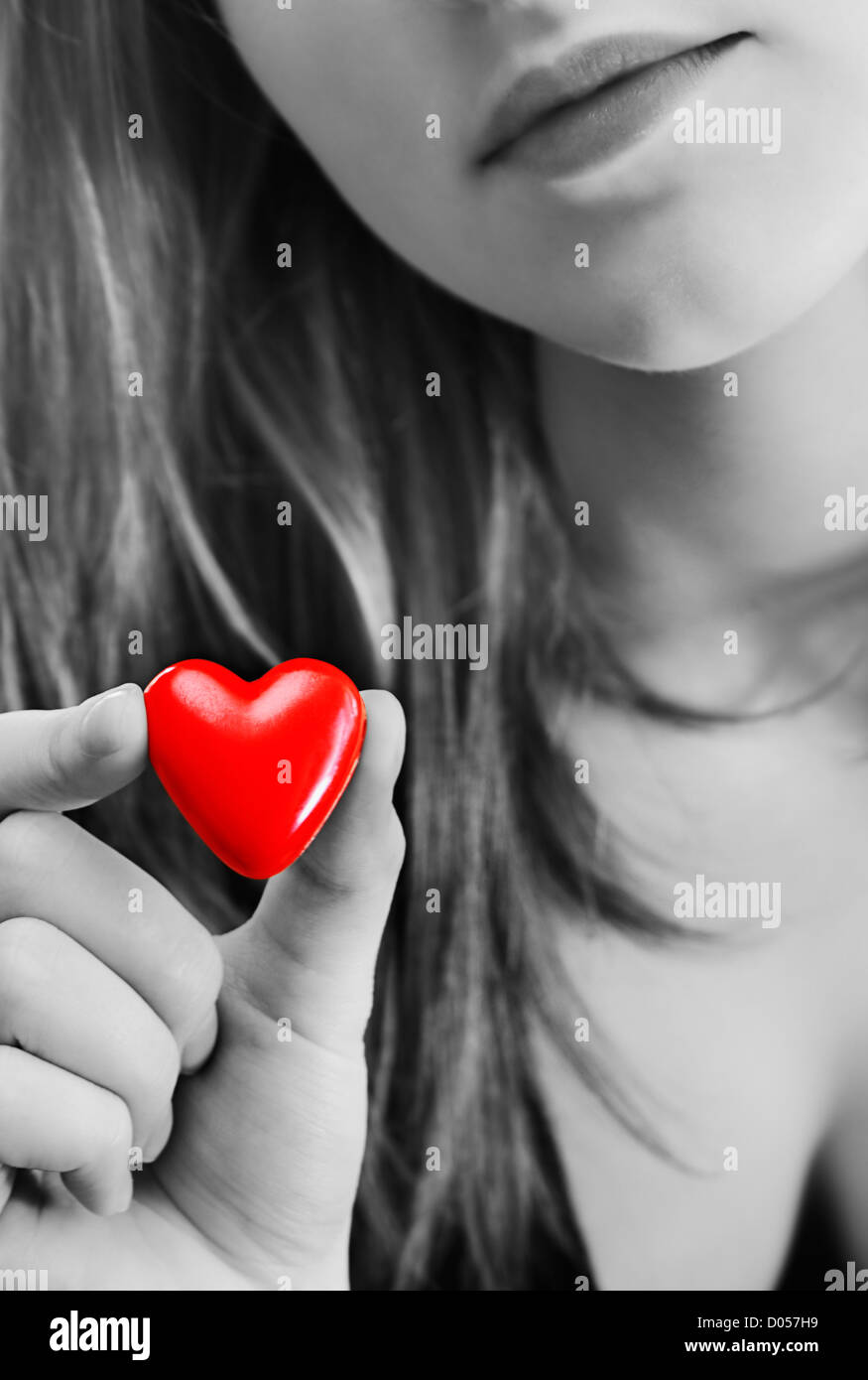 Girl holds in her hand a small red heart. Black-and-white image ...