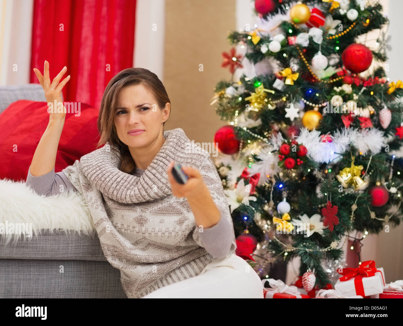 Frustrated woman with TV remote control near Christmas tree Stock ...
