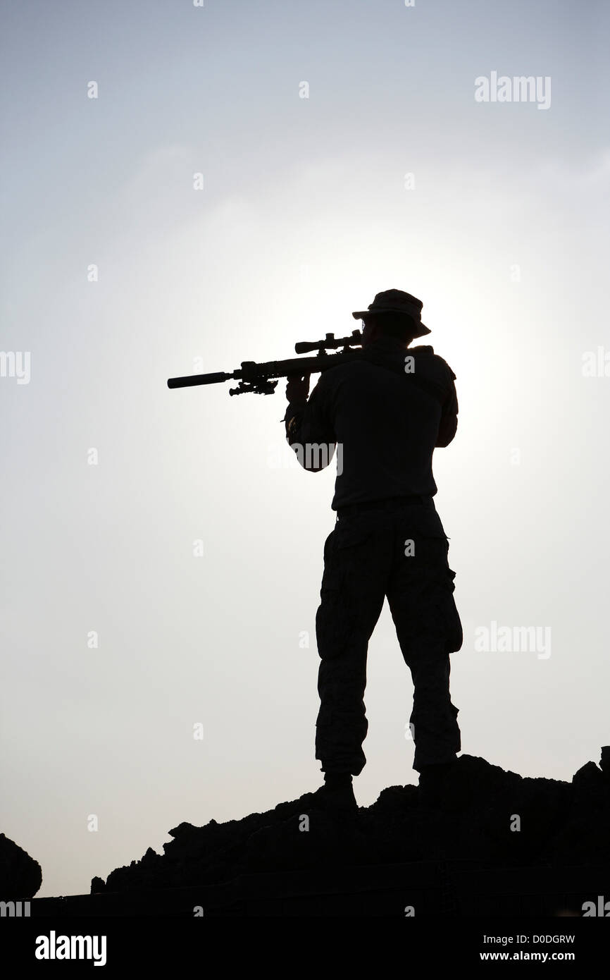Silhouette of a United States Marine aiming a rifle during ...