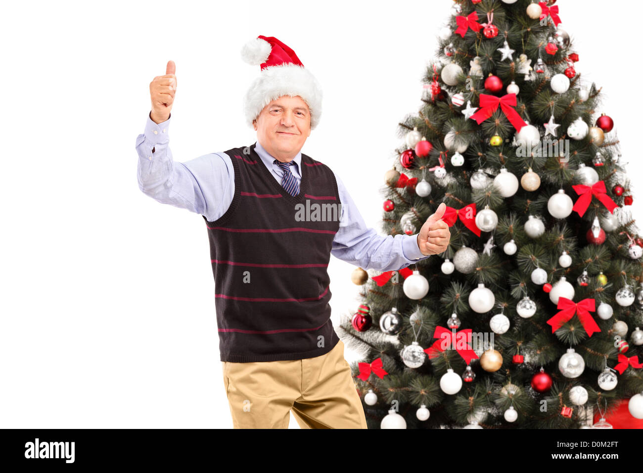 a happy mature gentleman giving thumbs up with christmas tree in the