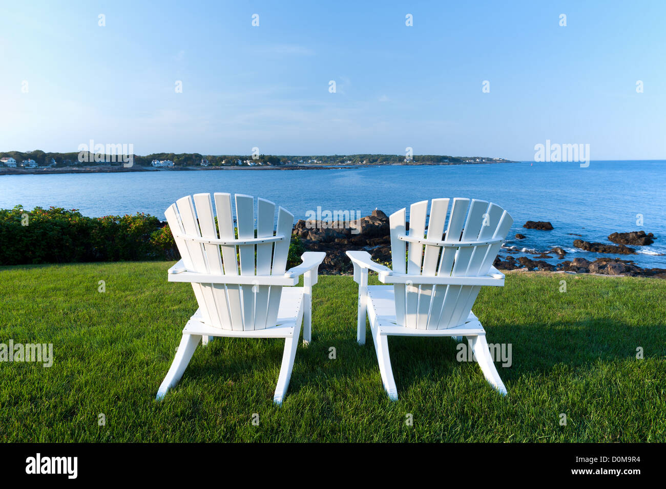 Two white Adirondack chairs on a lawn overlooking the Atlantic