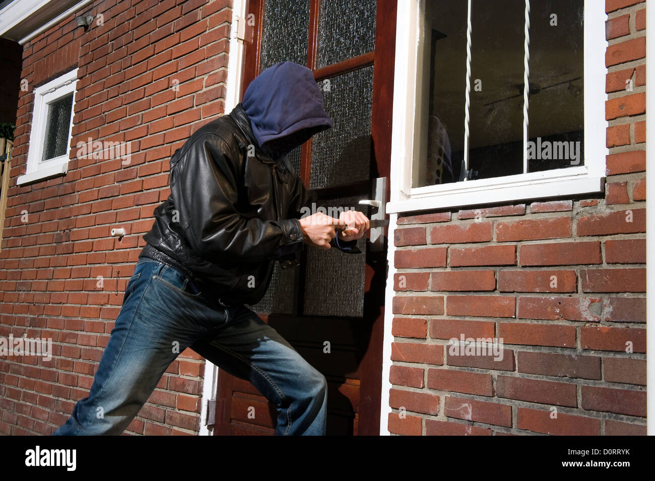 A burglar trying to get into a house by the back door & A burglar trying to get into a house by the back door Stock Photo ... Pezcame.Com