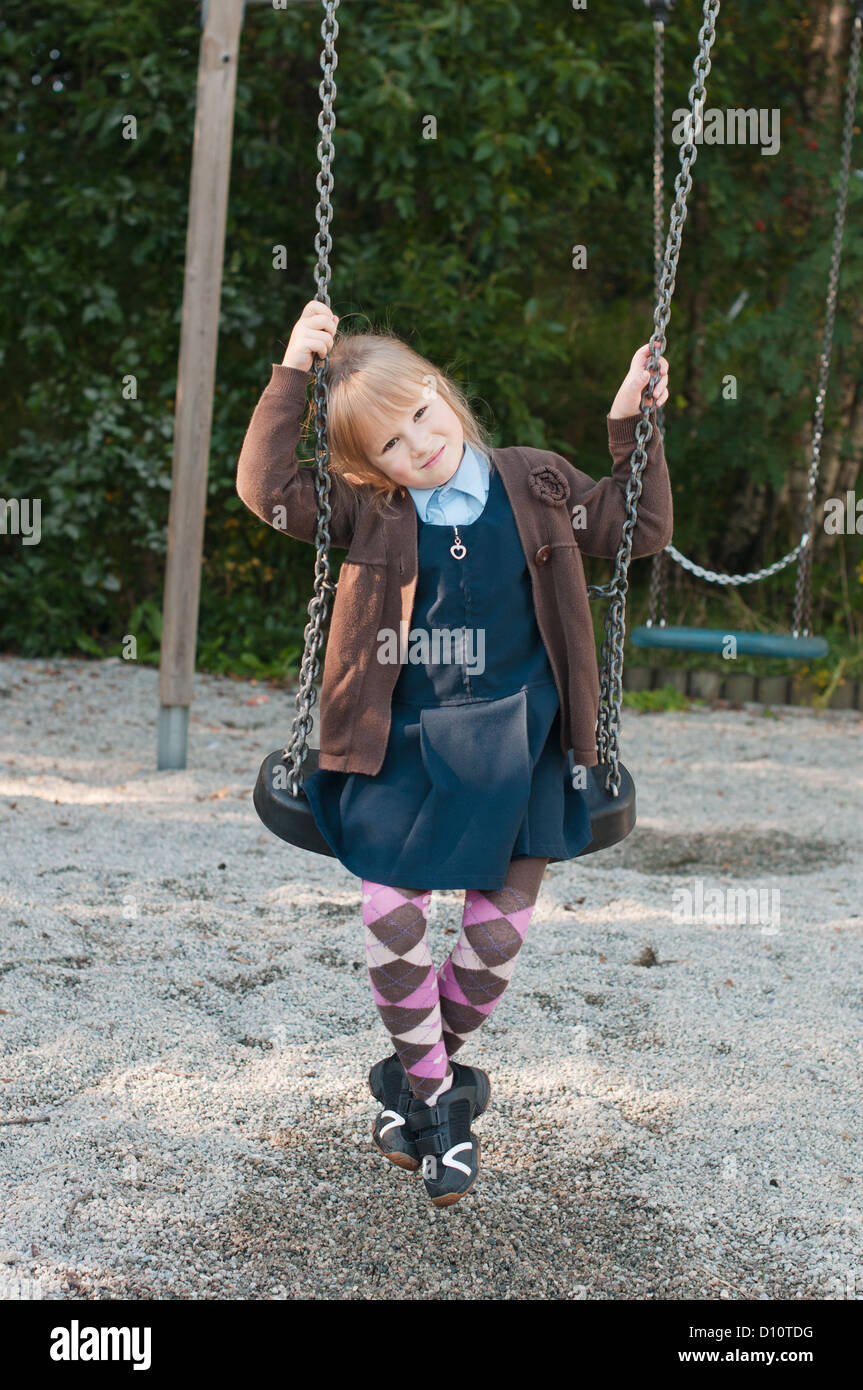 girl in british school uniform sitting on a swing Stock Photo ...