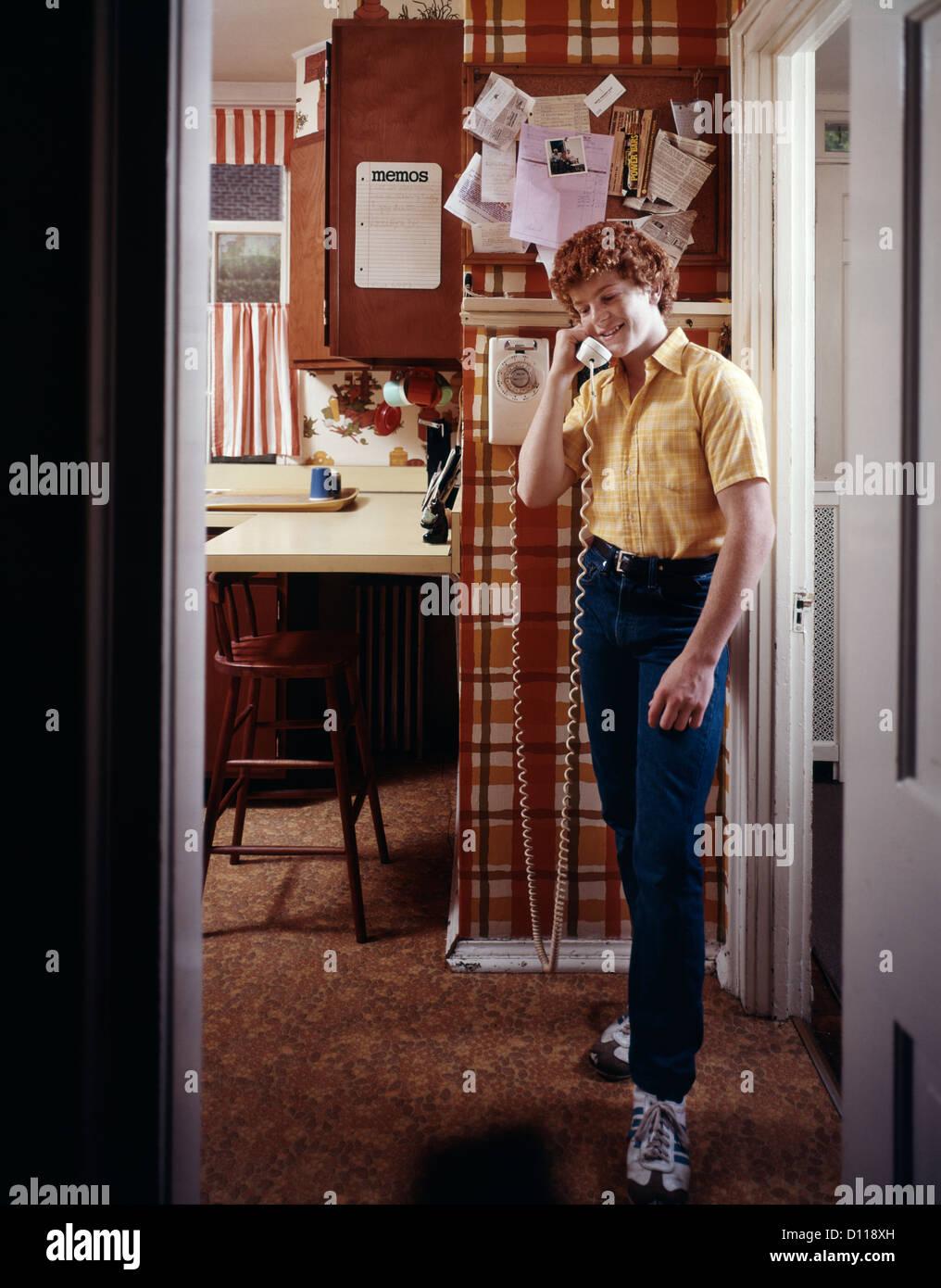 1970s TEENAGE BOY TALKING ON KITCHEN WALL PHONE TELEPHONE