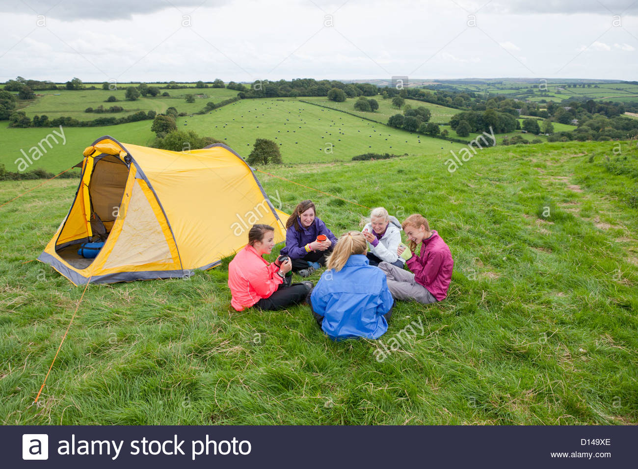 Girls sitting in circle and drinking tea next to tent in rural field & Girls sitting in circle and drinking tea next to tent in rural ...