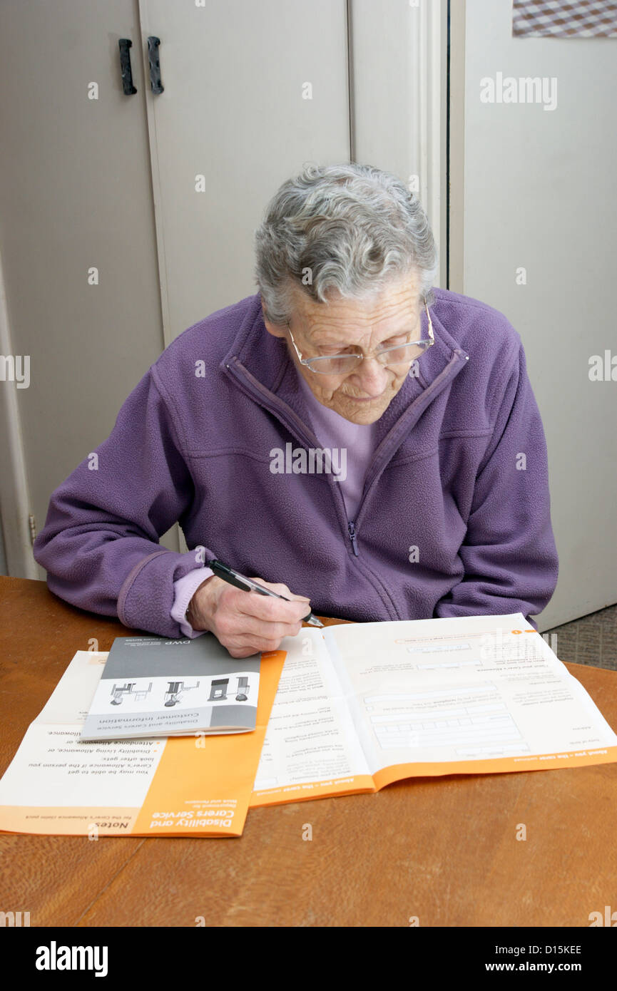 elderly w filling in an application form to claim for benefits elderly w filling in an application form to claim for benefits