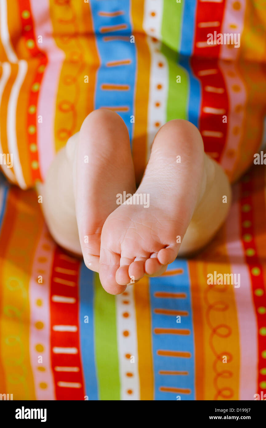 girlfeet toddlers girl feet in a bed with colorful duvet under the morning sun,  shallow DOF