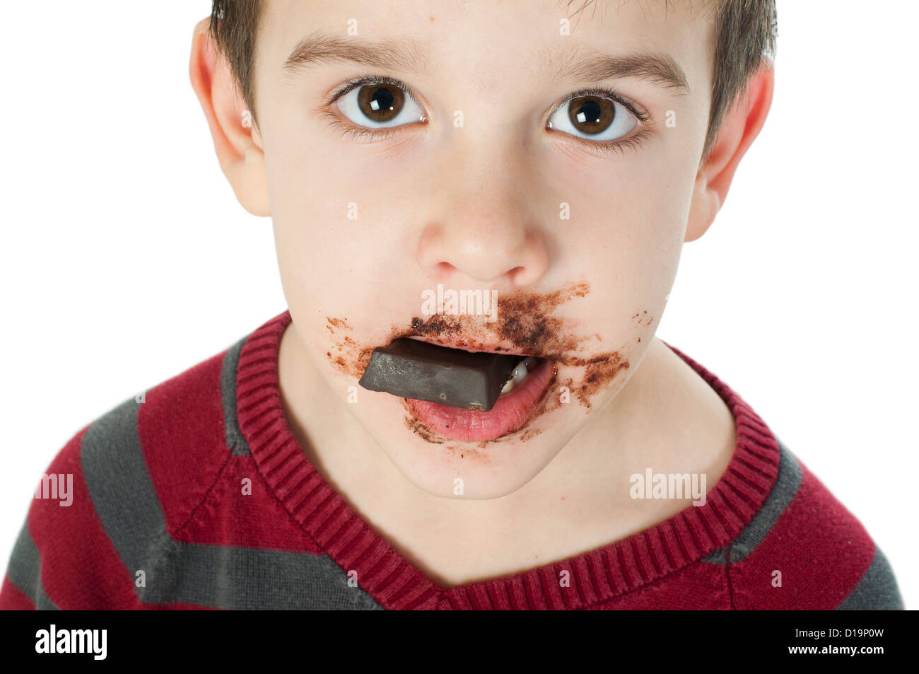 Smiling kid eating chocolate. Smeared stained with chocolate lips ...