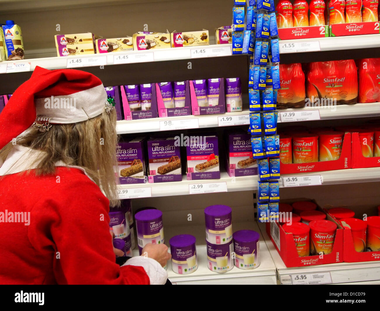 store assistant dressed as santa arranging the slimming foods on stock photo store assistant dressed as santa arranging the slimming foods on the shelves 2012