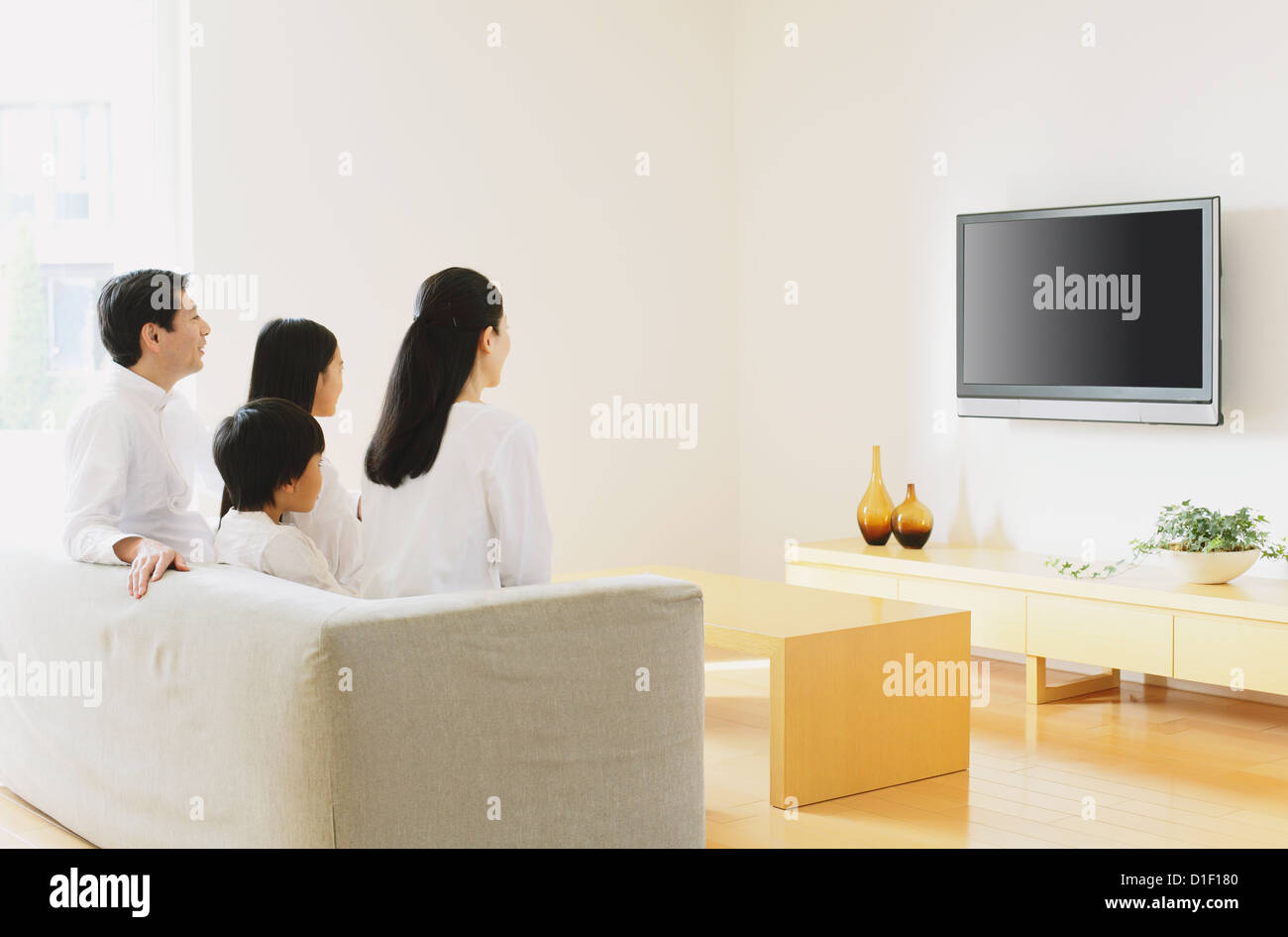 Family Of Four People Watching TV On The Sofa In Living Room