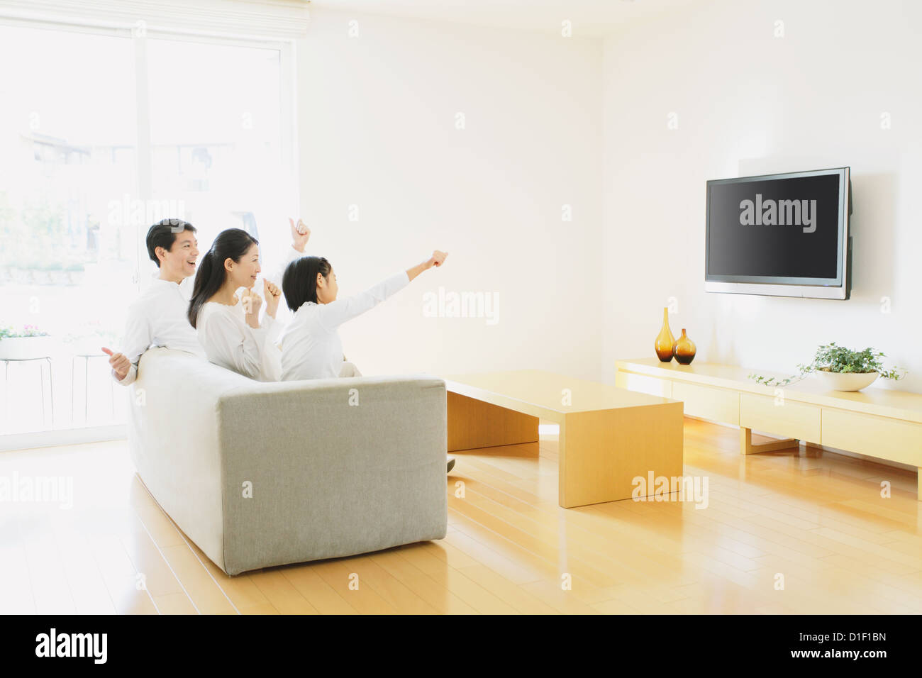 Family Of Three People Watching TV On The Sofa In Living Room