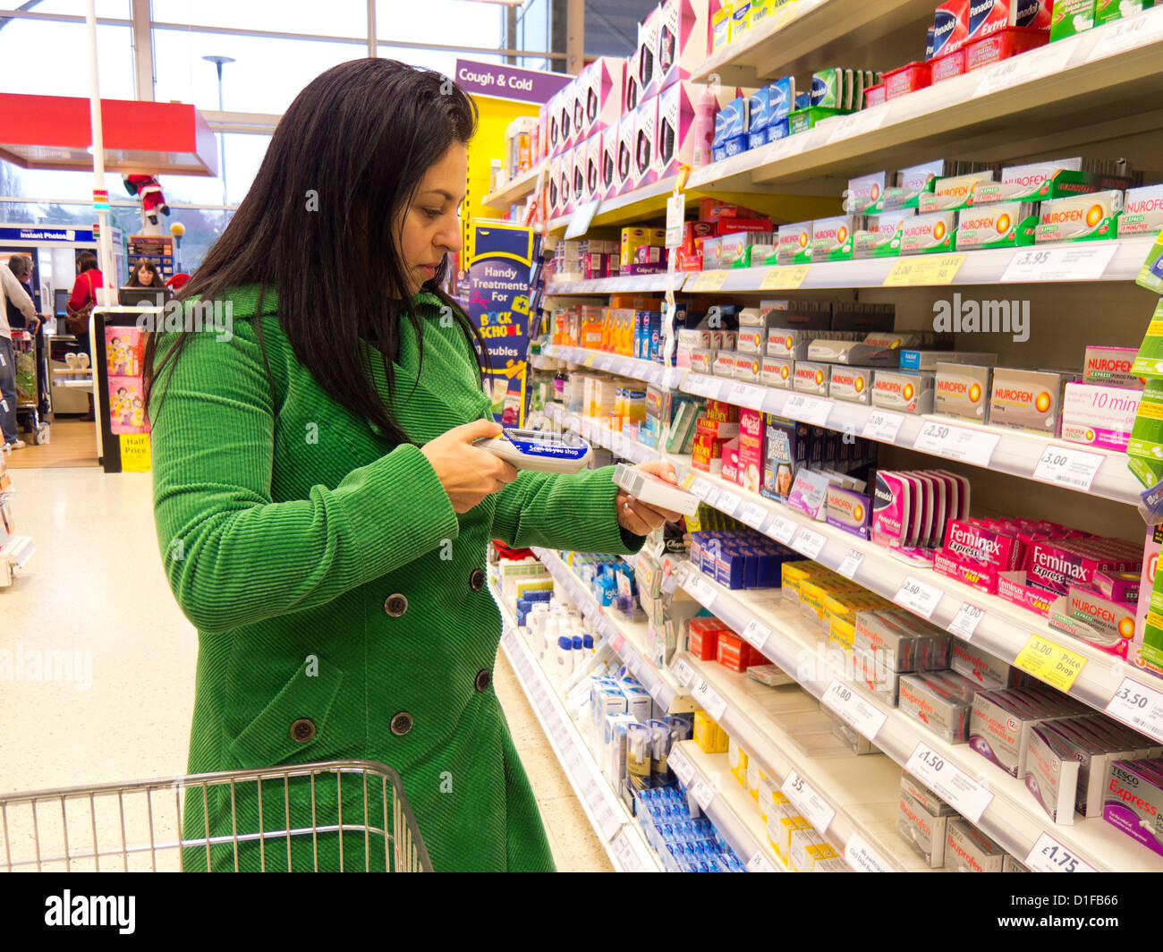 Woman using handheld scan as you shop barcode scanner in ...