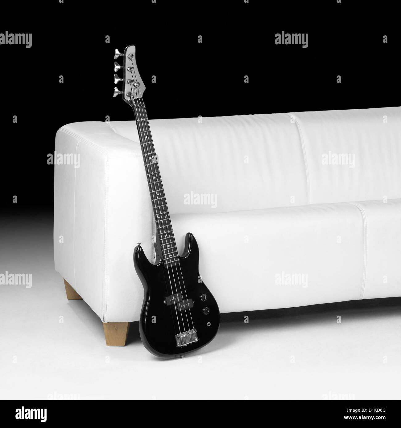 Black Bass Guitar Lean Against White Couch In Dark Back