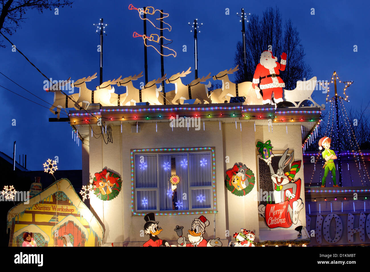 santa and his reindeer on top of house lit up for annual christmas