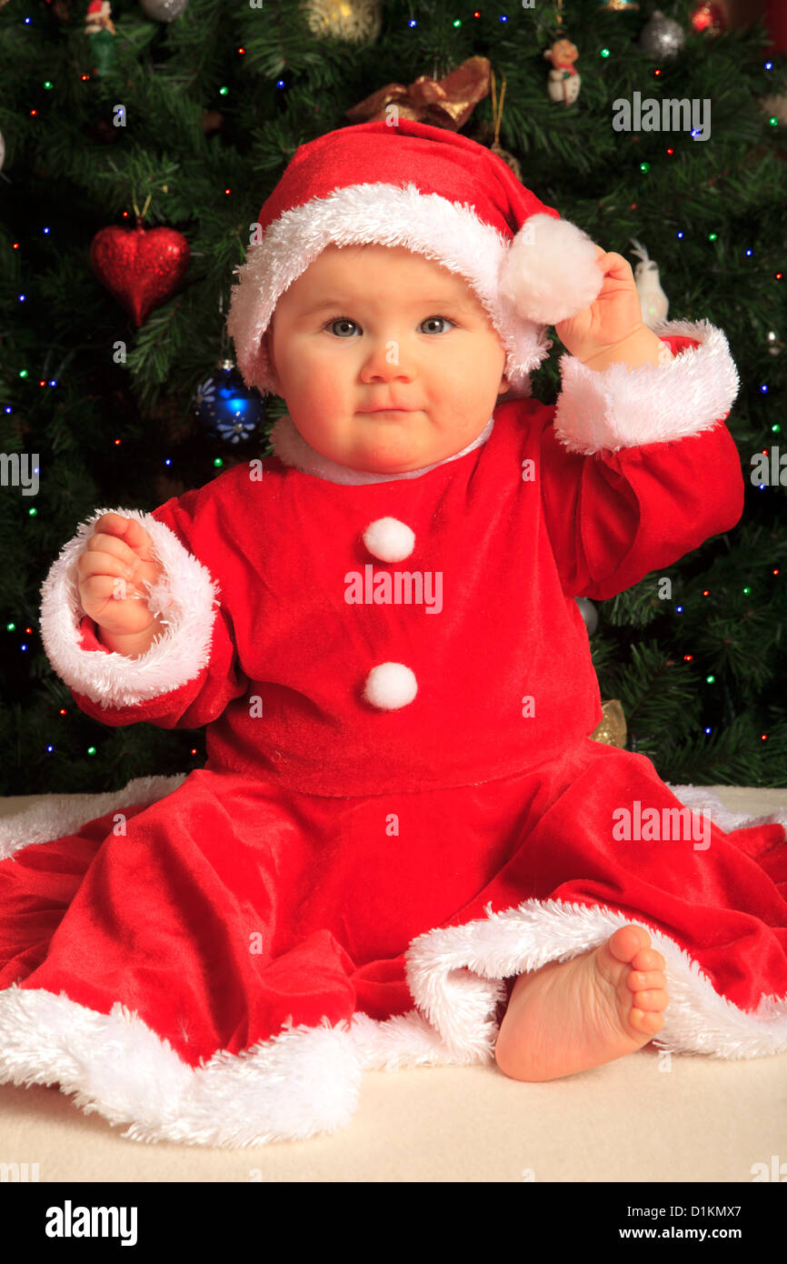 8 Month Old Baby Girl Dressed Like Santa Claus In Front Of