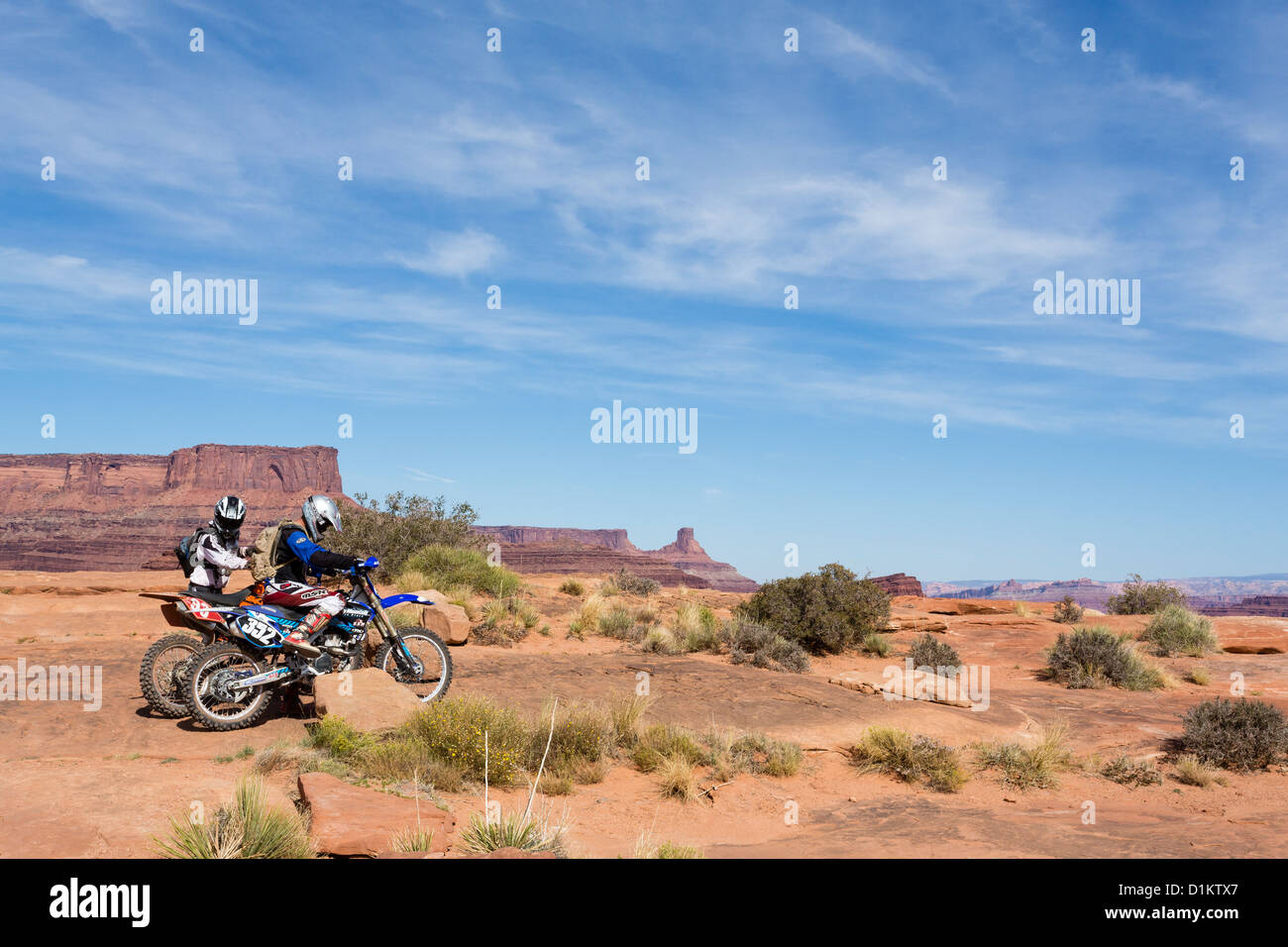 two bikers riding dirt bikes at the canyonlands national. Black Bedroom Furniture Sets. Home Design Ideas