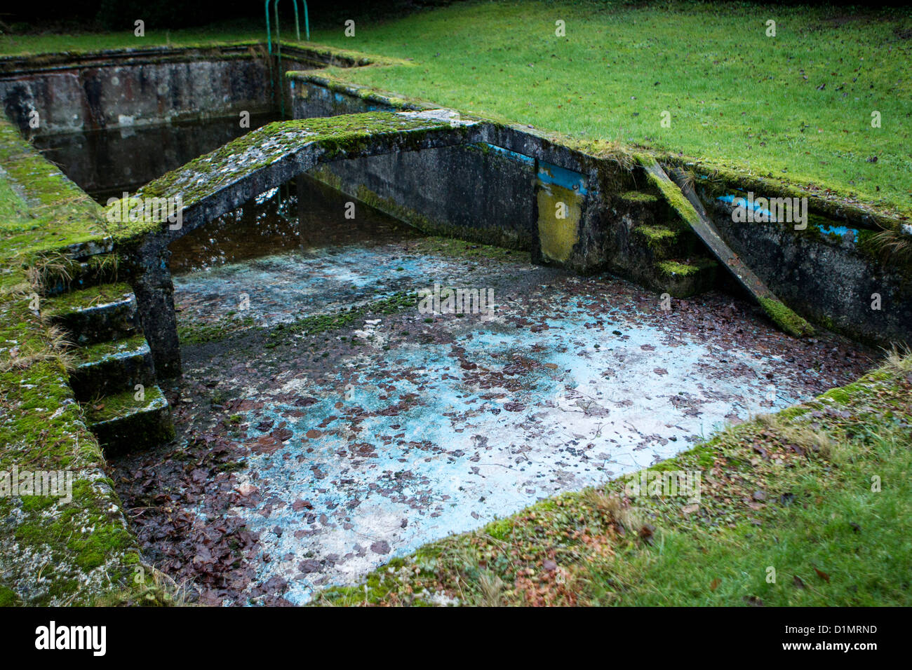 An empty and ruined outdoor swimming pool covered in moss for Disused swimming pools