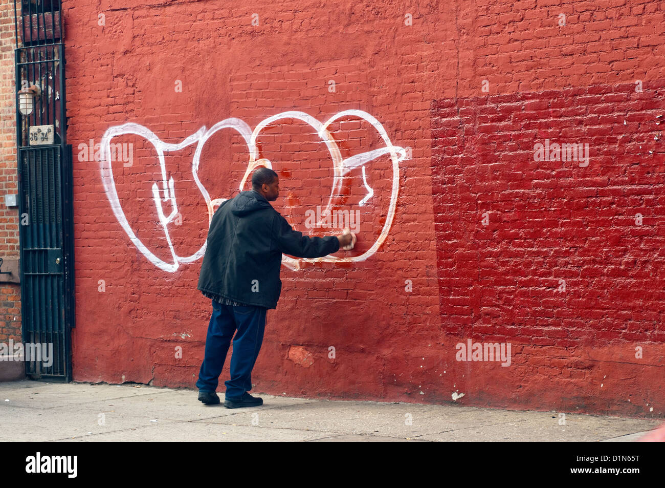 Grafiti wall red - New York Ny 23 December 2012 Man Cleaning Graffiti Off A Red Brick Wall On Barrow Street In The West Village