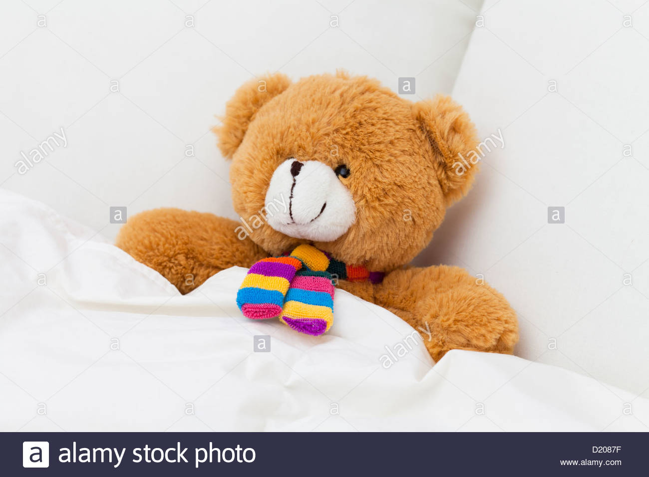 teddy bear sleeping in a bed stock photo royalty free image