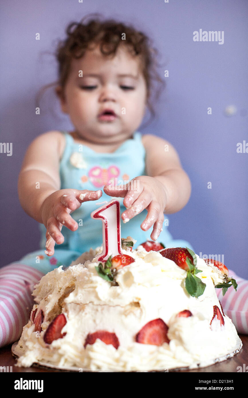 Cute baby girl with a birthday cake and number one candle Stock