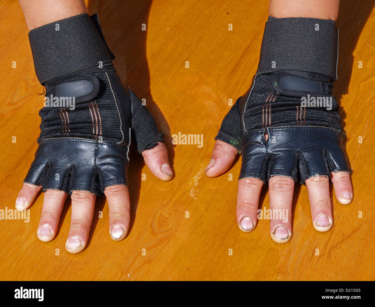 Black leather gloves with coloured fingers - Hands In Black Leather Gloves Without Fingers For Weight Lifting Close Up