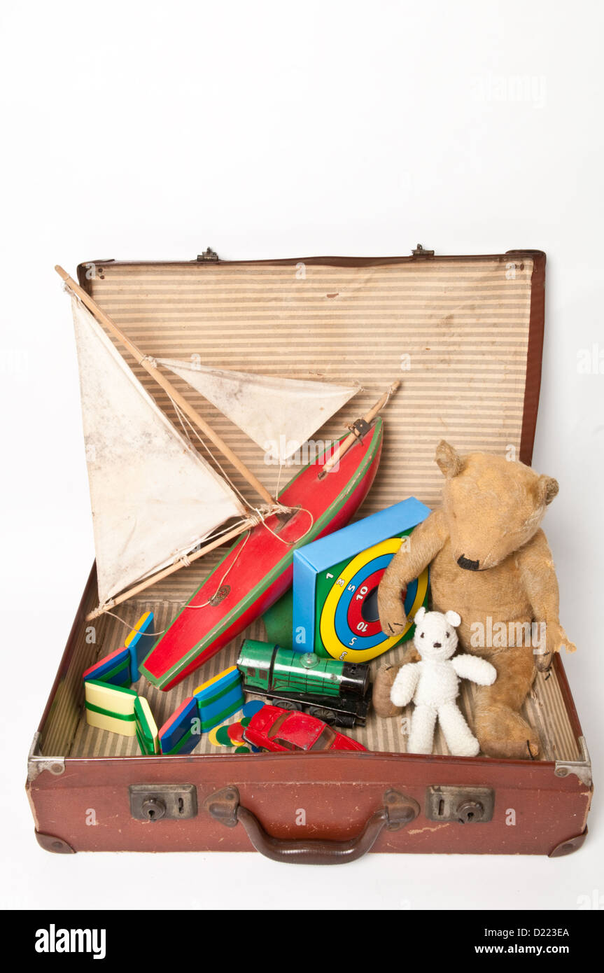 A battered old brown suitcase filled with vintage children's toys ...