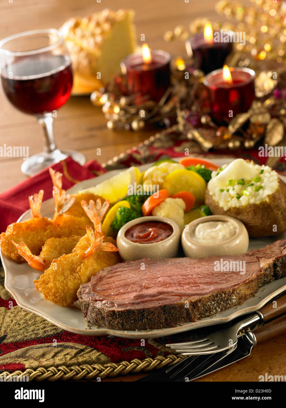 Prime Rib And Fried Shrimp Dinner With Baked Potato Vegetables And Red Wine In A Holiday Setting