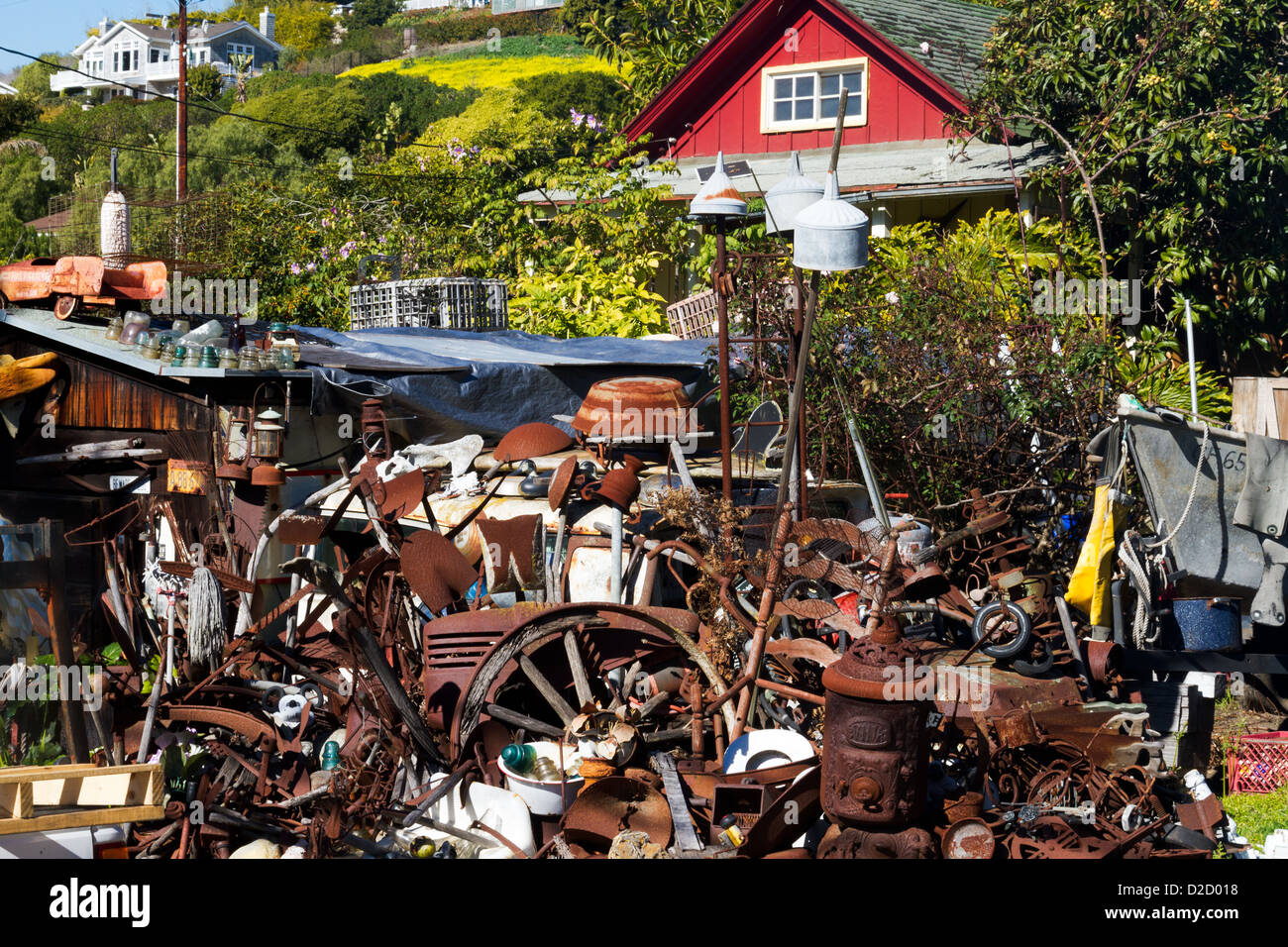 Front yard of a red painted house piled up with junk as an ...