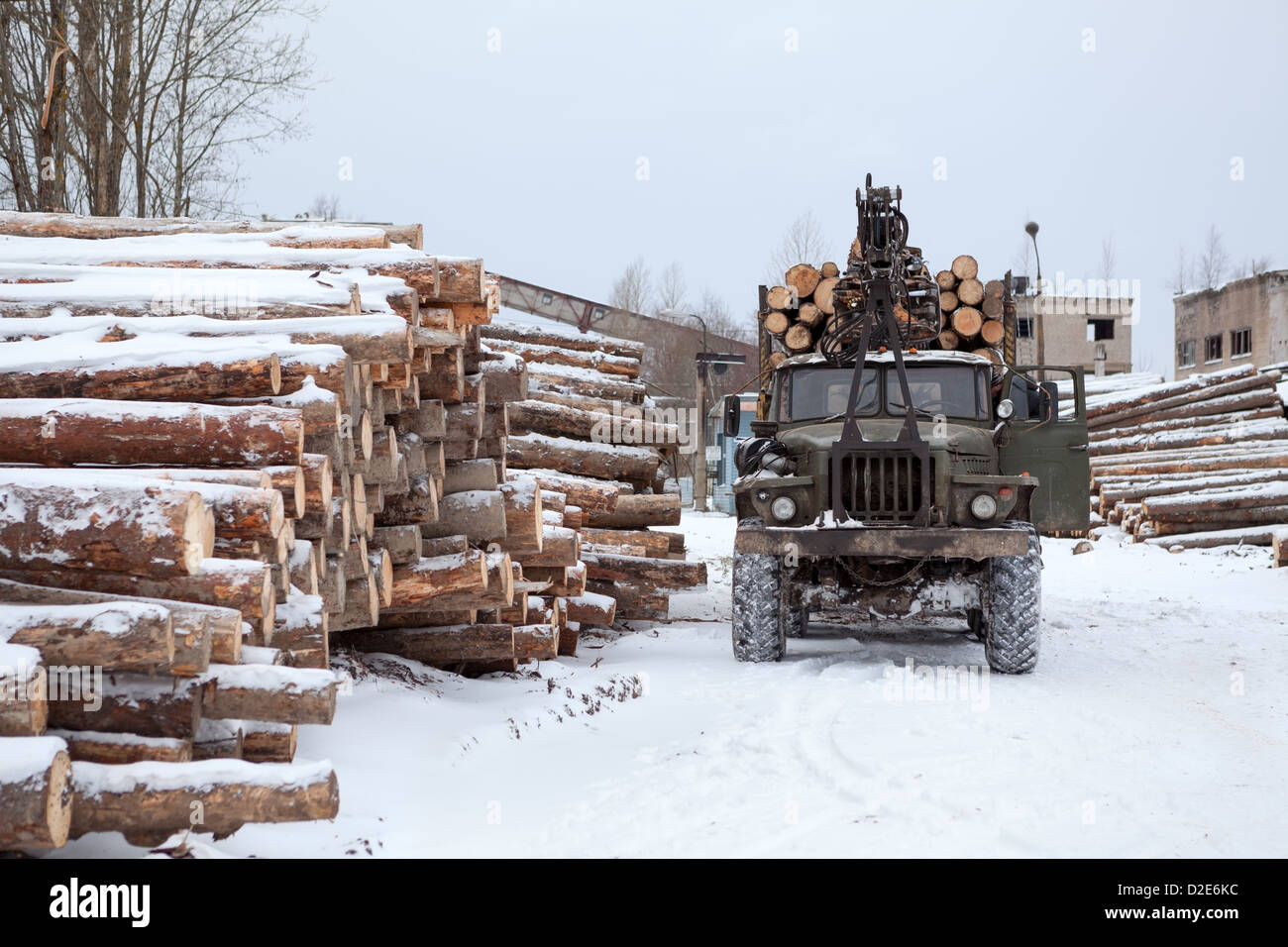 Log loader track with timber in lumber mill winter