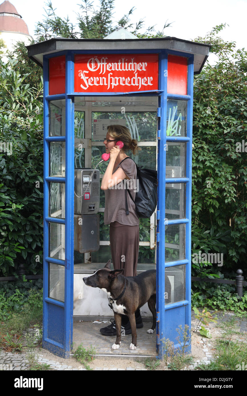 berlin germany a woman phoned in an old fashioned phone booth stock photo royalty free image. Black Bedroom Furniture Sets. Home Design Ideas