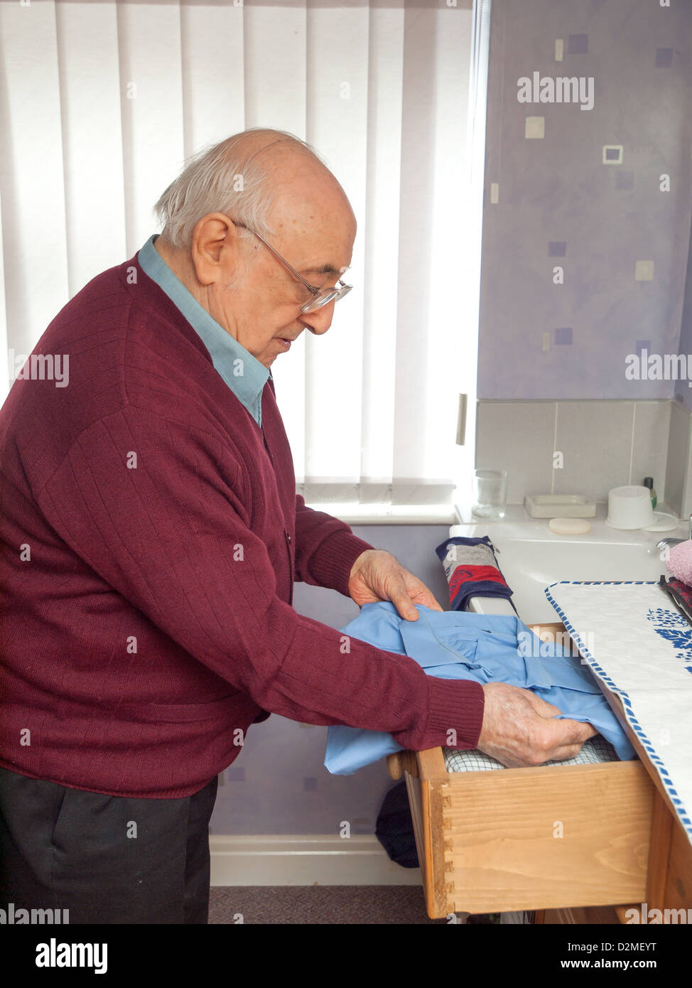 Put Clothes Away ~ Elderly man putting away clothes in wooden drawers stock