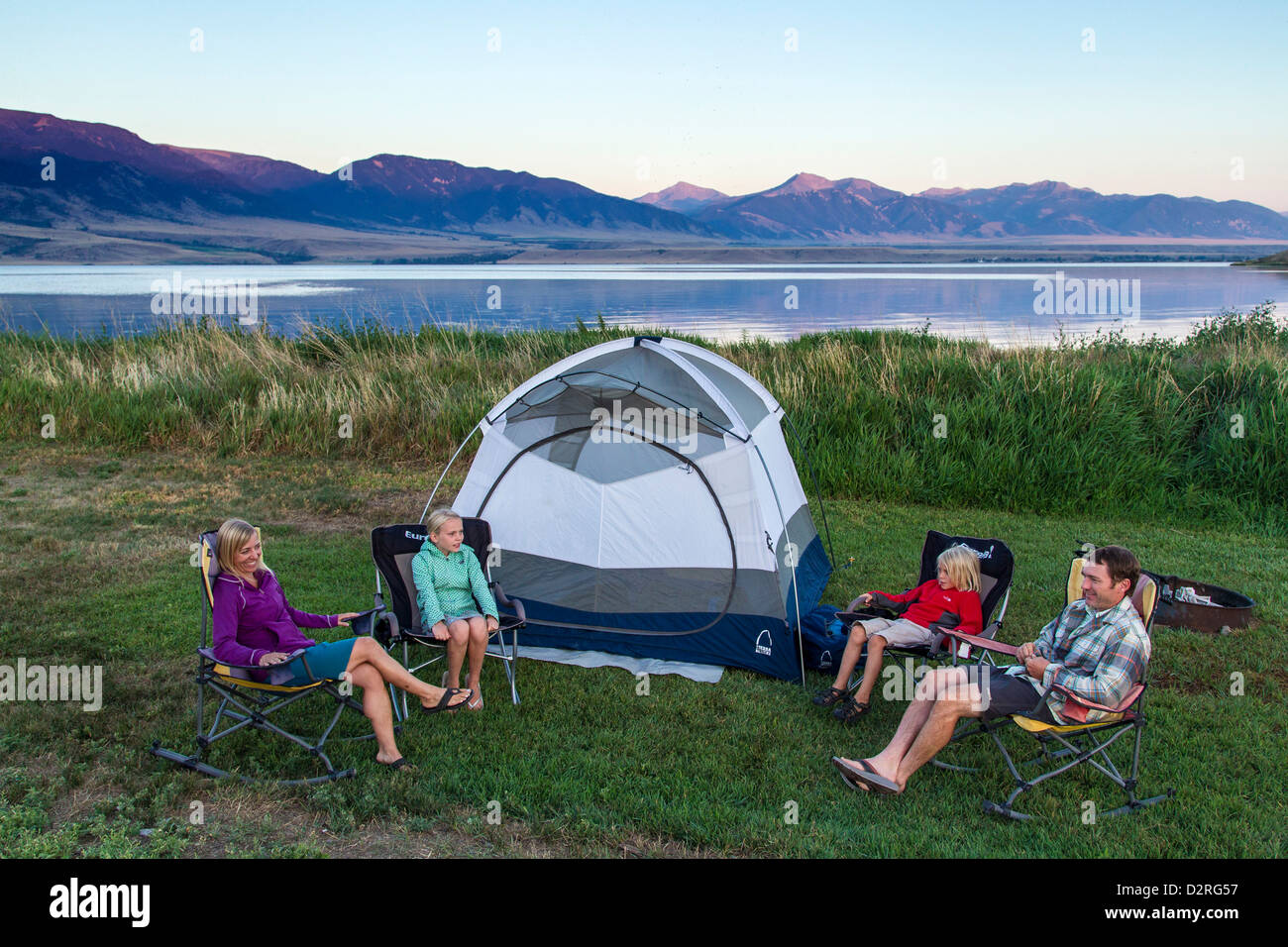 Family sits around the tent while c&ing at Ennis Lake near Ennis Montana USA. (MR & Family sits around the tent while camping at Ennis Lake near Ennis ...