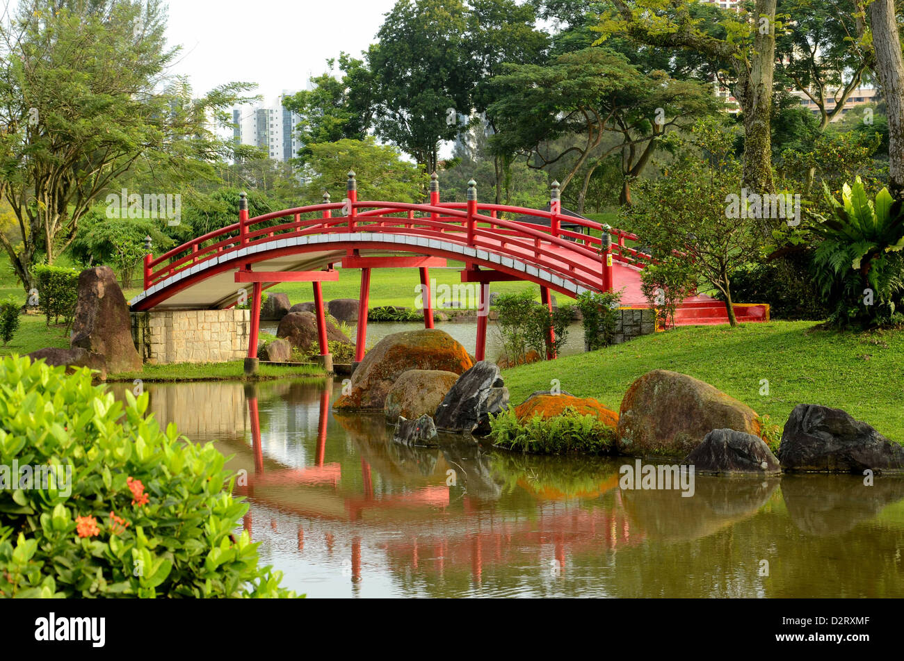 picturesque curved red japanese style bridge over stream