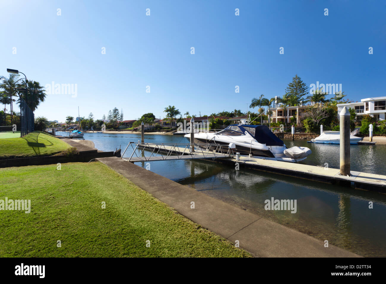 waterfront backyard with tennis court and luxury yacht stock photo