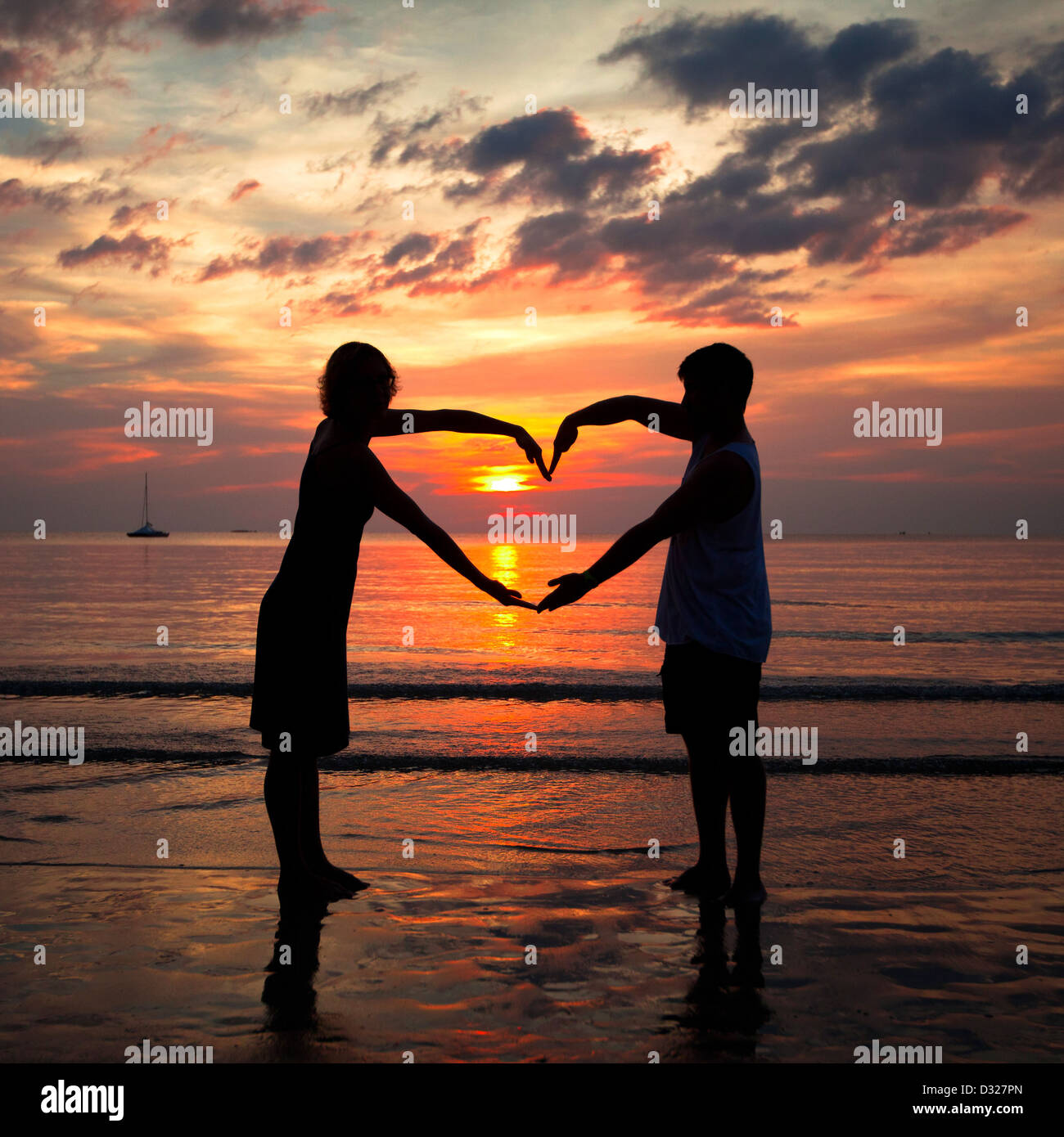 Young Couple Holding Hands Heart Shaped On The Sea Beach At Sunset