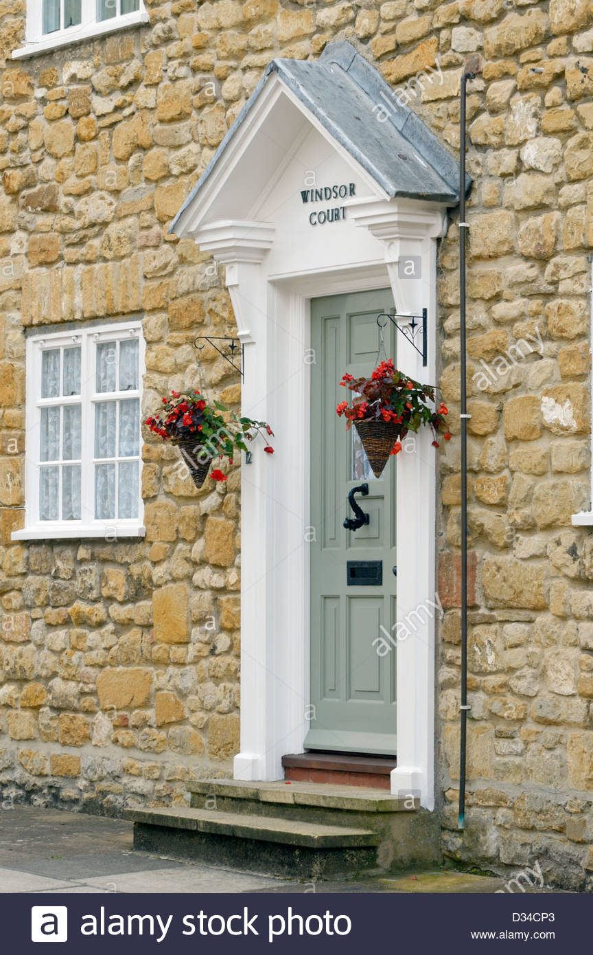 Front door of house with steps small canopy side pillars and hanging baskets Sherborne Dorset England & Front door of house with steps small canopy side pillars and ...