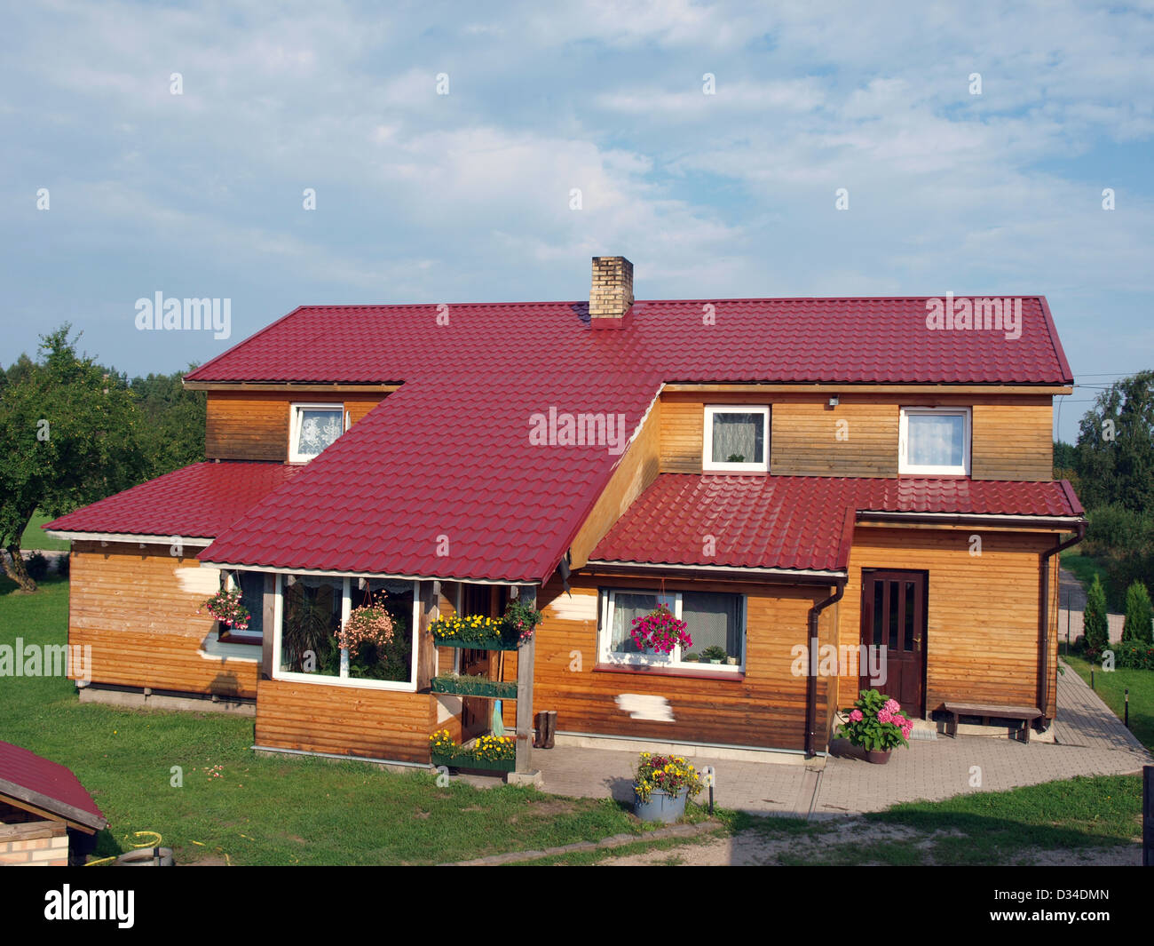 Country House With Wooden Walls And Red Metal Roof