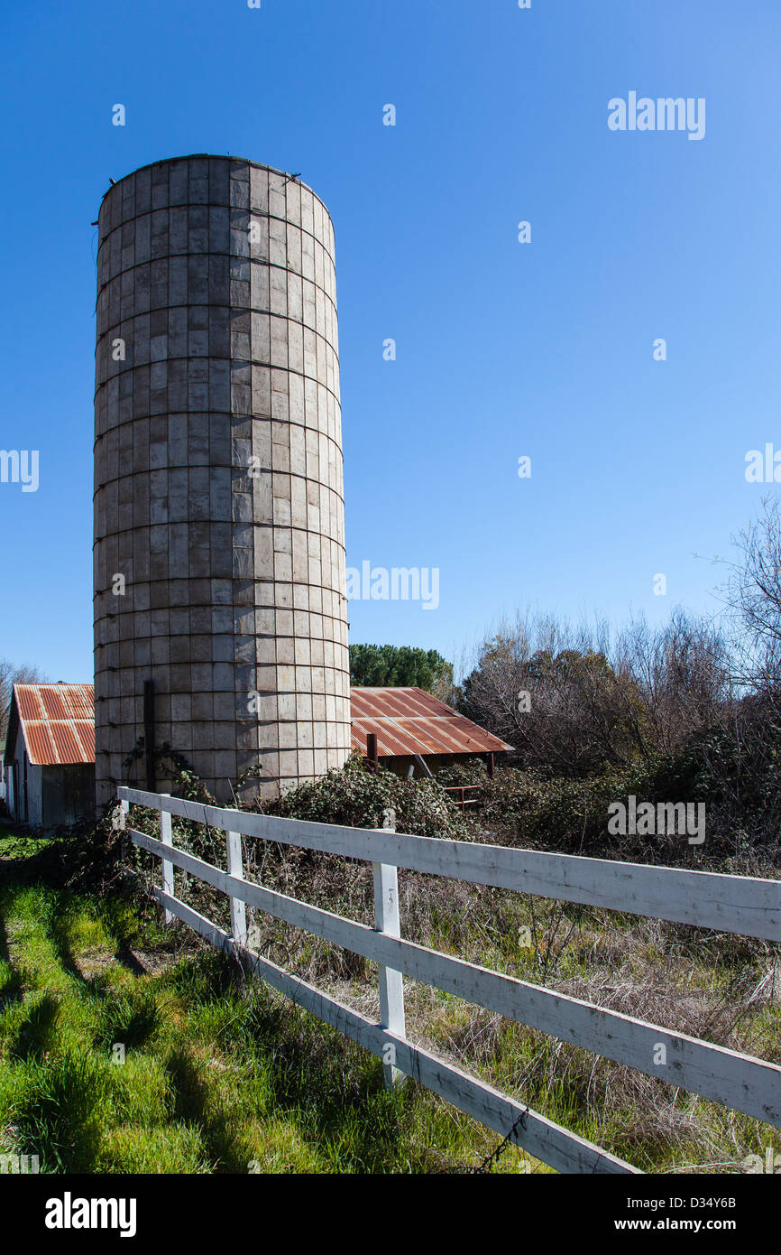 A Concrete Silo And Rusted Metal Roof Of A Farm Building In The Background  And White Rail Fence In Foreground In Santa Ynez, CA.