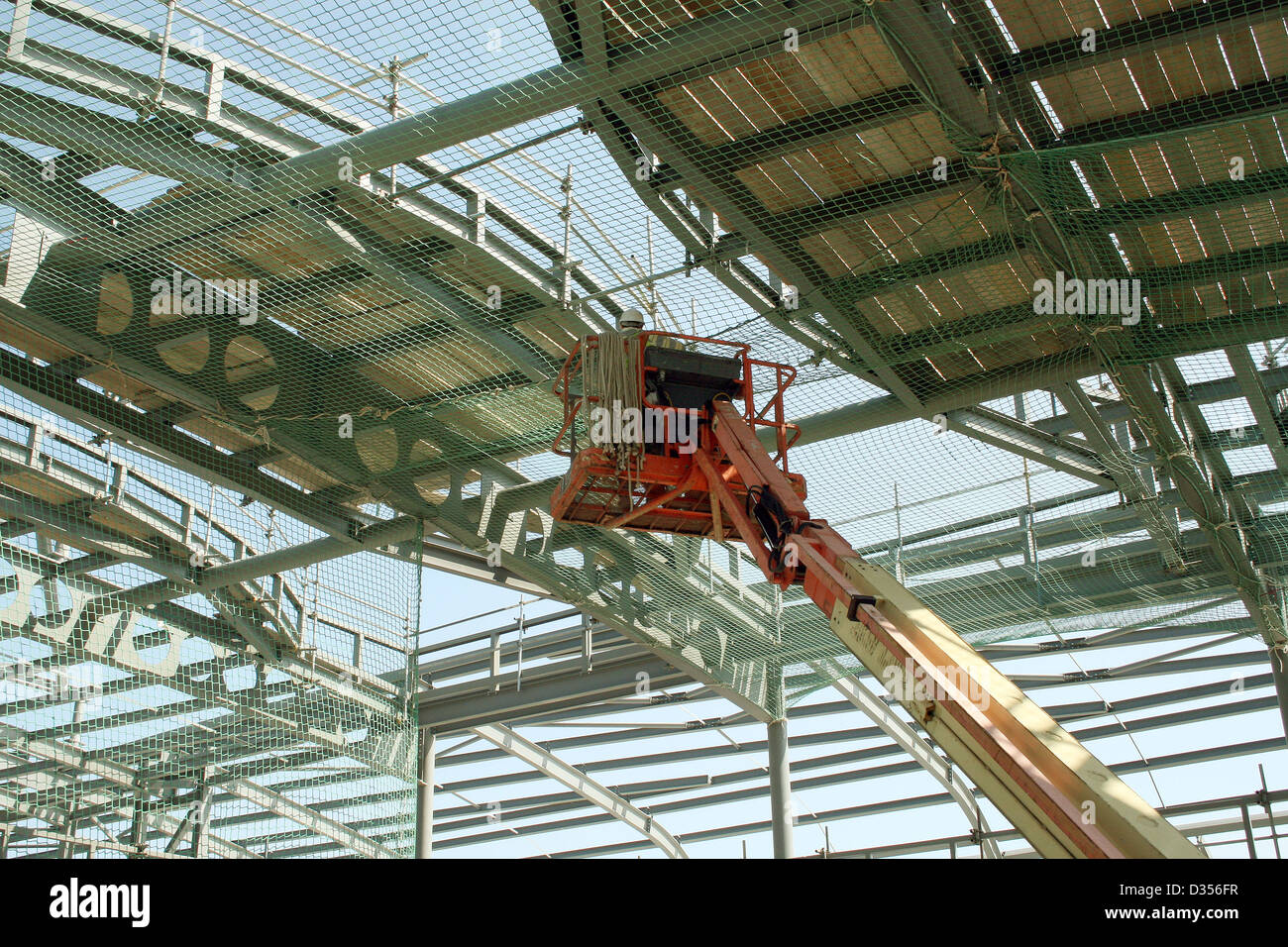 Man Working At Heights In A Cherry Picker Erecting A