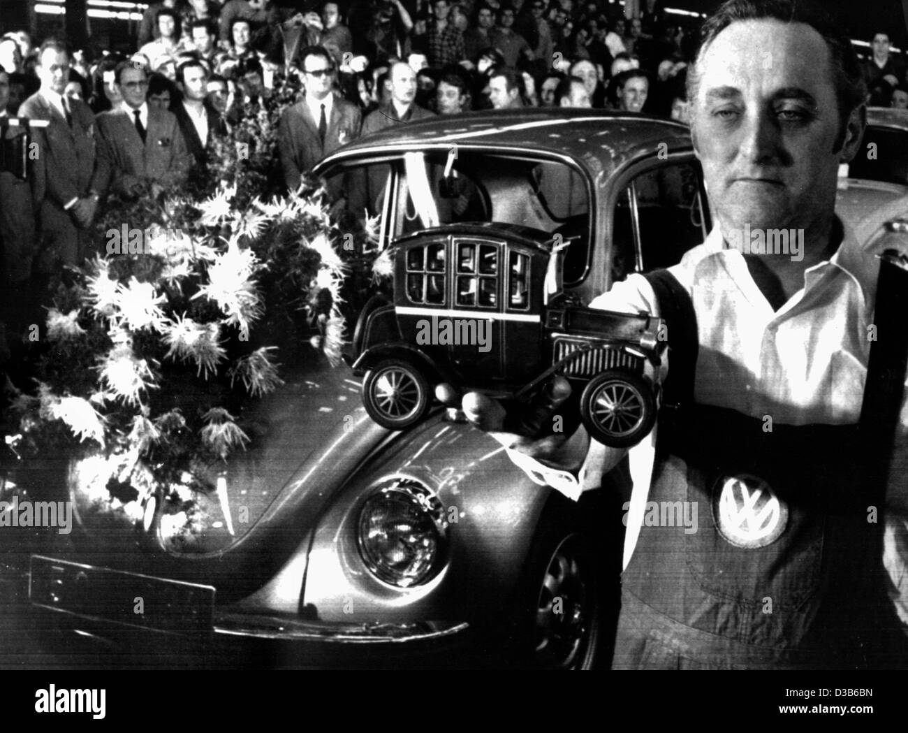 dpa files a vw worker presents a model of the ford model t in front of the 15 007 034th vw beetle in the volkswagen factory in wolfsburg west germany