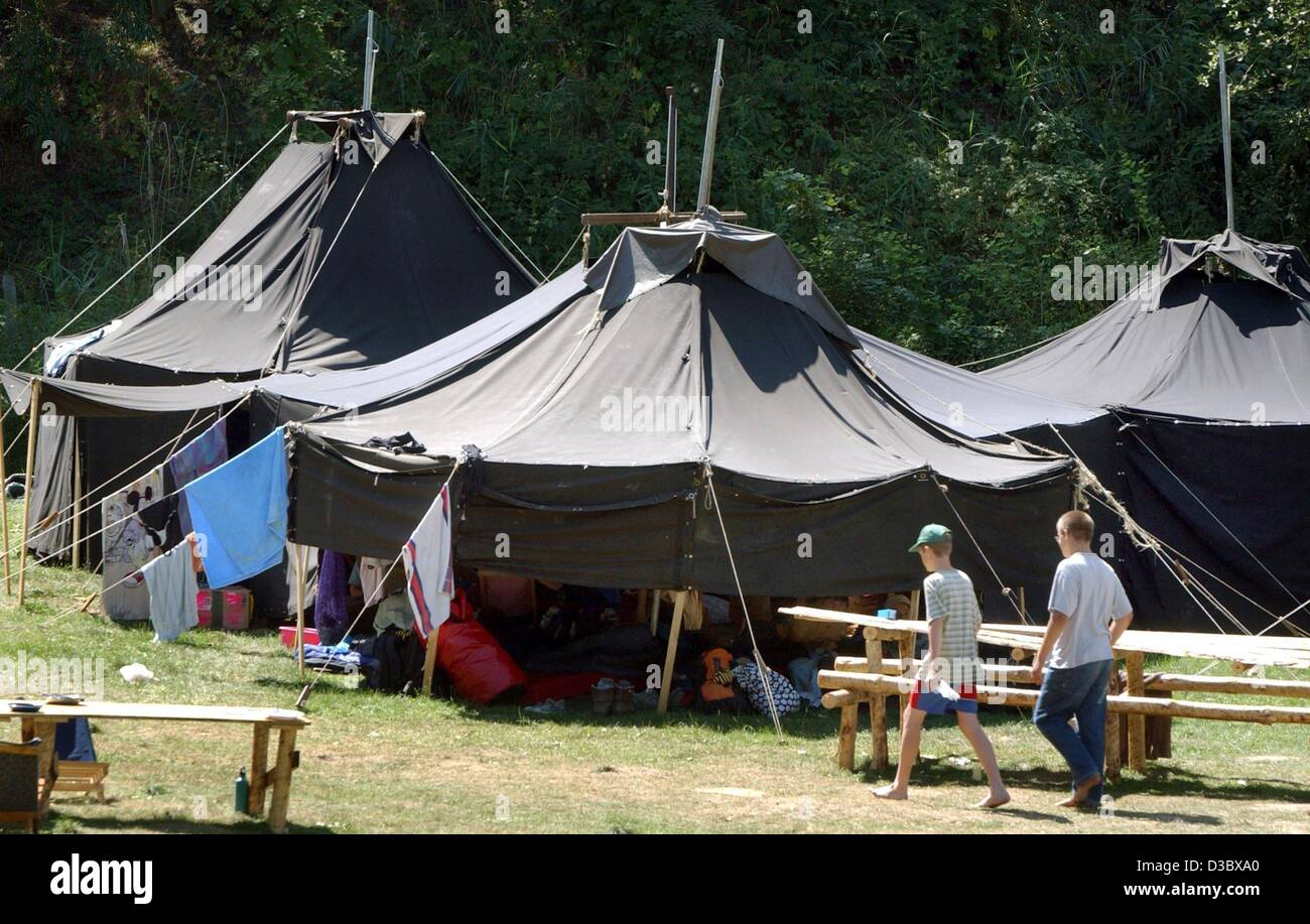 (dpa) - Two boys walk past a group of tents during a c& meeting & dpa) - Two boys walk past a group of tents during a camp meeting ...
