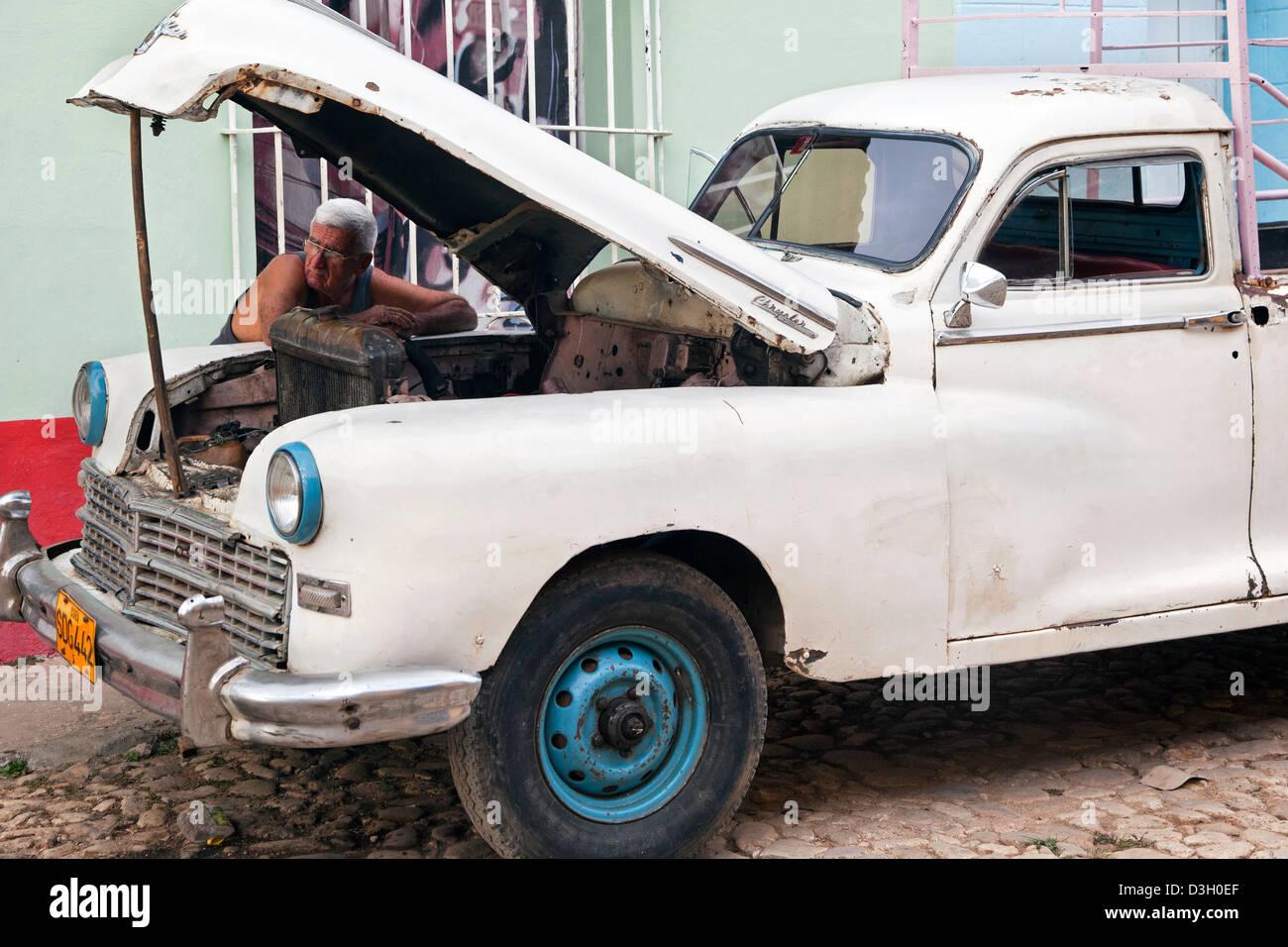 Cuban car mechanic repairing 1950s vintage American Chrysler ...